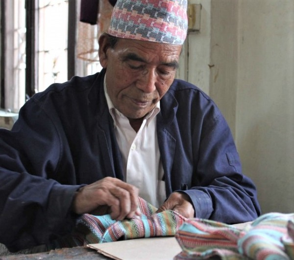 Nepali artisan cutting the material